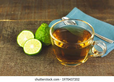 Bergamot tea or Earl Grey tea in transparent cup and fresh bergamot fruit with sliced on wooden table.
