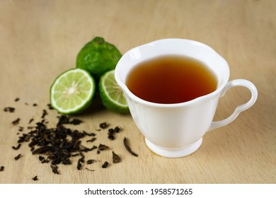Bergamot tea or Earl Grey tea in white cup and fresh bergamot fruit with sliced on brown wooden table.