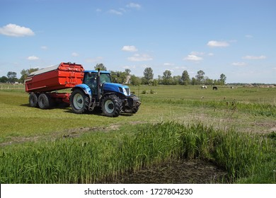 Bergen, Netherlands, May 4, 2020. Pasture landscape. A blue tractor with a red trailer coupled behind it in a meadow near the Dutch village of Bergen in the spring.