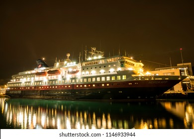 "Bergen, Norway - 04 April 2018: The illuminated Hurtigruten cruise ship ""MS NORDKAPP"" is about to leave the port of Bergen at night."