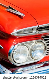 BERGEN, NORWAY - 4/29/18: Close up  view of the circular headlight, shiny metal arrow hood element, chrome grill and front bumper of a 1959 Chevrolet Impala, during an amcar owners meeting.