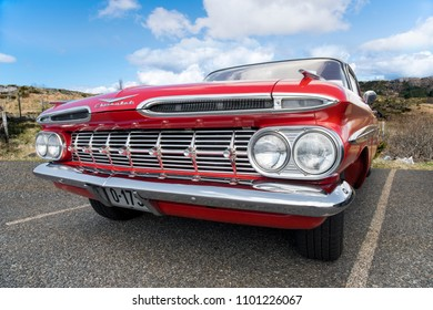 BERGEN, NORWAY - 4/29/18: Full low front side view of a red 1959 Chevrolet Impala, parked in a mountain tourist area during an amcar owners meeting.