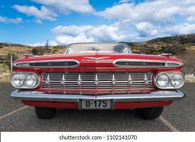 BERGEN, NORWAY - 4/29/18: Full low front view of a red 1959 Chevrolet Impala, parked in a mountain tourist area during an amcar owners meeting.