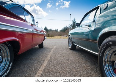 BERGEN, NORWAY - 4/29/18: Low side view of a 1969 Ford Mustang and 1959 Chevrolet Impala,  parked in a mountain tourist area during an amcar owners meeting on a sunny spring day.