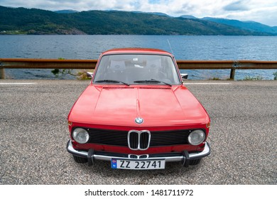 Bergen, Norway -  8/3/19: Full frontal view of a german classic - 1975-1977 BMW model 1502 2 door, parked outside with the Hardanger fjord in the background.