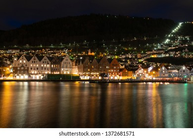 Bergen Norway April 03 2019: Bryggen Wharf/Tysk Bryggen, old hanseatic quarter with brightly colored historic wooden houses and shops at night in spring, reflection on water unesco world heritage site