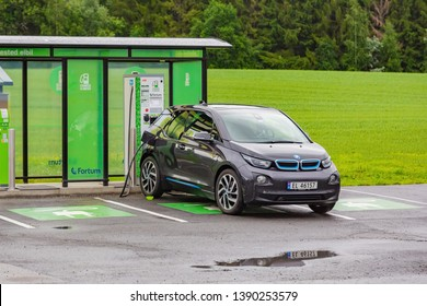 Bergen, Norway - Jule, 2016: EV Car or Electric car at charging station with the power cable supply plugged in on nature background. Charging modern electric car.
