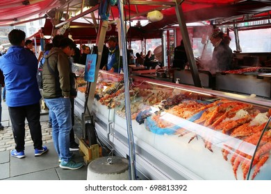 Bergen, Norway - July, 03, 2017: People selling sea food products to a customers in the fish market of Bergen