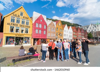 BERGEN, NORWAY - JULY 28, 2018: Tourists in front of the historical buildings in Bryggen- Hanseatic wharf. Bryggen has been on the UNESCO World Heritage List since 1979.