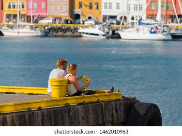 BERGEN, NORWAY - JULY 28, 2018: Unknown love couple in front of the historical buildings in Bryggen- Hanseatic wharf. Bryggen has been on the UNESCO World Heritage List since 1979.