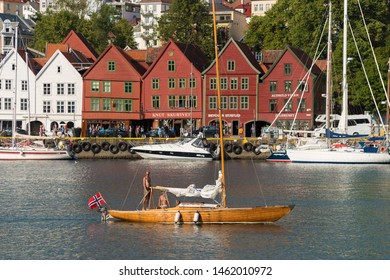 BERGEN, NORWAY - JULY 28, 2018: Sail boat passing by the historical buildings in Bryggen- Hanseatic wharf. Bryggen has been on the UNESCO World Heritage List since 1979.