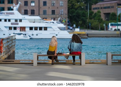 BERGEN, NORWAY - JULY 28, 2018: Two unknown young women sitting on the Bergen pier enjoying the nice view