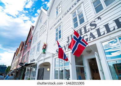 BERGEN, NORWAY - JULY 28, 2018: Norwegian flags hanging on the facade of a store at the famous Bryggen promenade