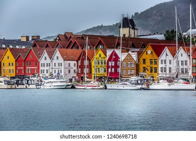 Bergen, Norway - July 30, 2018: City street view with Bryggen Hanseatic Wharf, boats and colorful traditional nordic houses