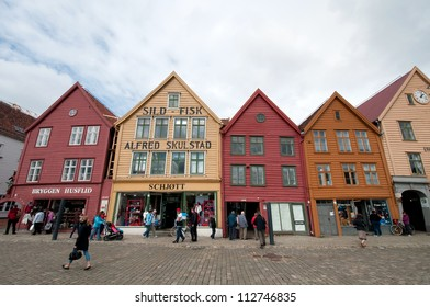 BERGEN, NORWAY - JUNE 15: Tourists and locals stroll along the UNESCO World Heritage Site, Bryggen, in the city of Bergen, on June 15, 2011. Bryggen is famous for its old wooden buildings and history.