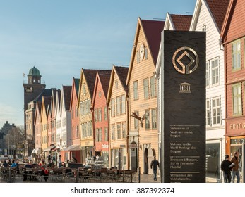BERGEN, NORWAY - MARCH 31, 2014: Unesco World Heritage Site Silver Sign on Black Sandstone in Norwegian (Norsk), English, French, German with Out of Focus Bryggen under Clear Blue Sky Sunny Day