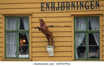 "BERGEN, NORWAY - MAY, 2019: Historical building of Restaurant ""Enhjørningen"" (""The Unicorn"") and sign of unicorn on it in Bryggen - Hanseatic wharf in Bergen, Norway. UNESCO World Heritage Site."