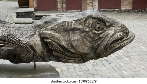 BERGEN, NORWAY - MAY, 2019: Historical buildings in Bryggen - Hanseatic wharf in Bergen, Norway. UNESCO World Heritage Site. Sculpture of a tadpole fish made of wood in wharf street.