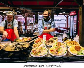 Bergen, Norway - Sep 9 2018: Two men selling seafood at fish market in Bergen.