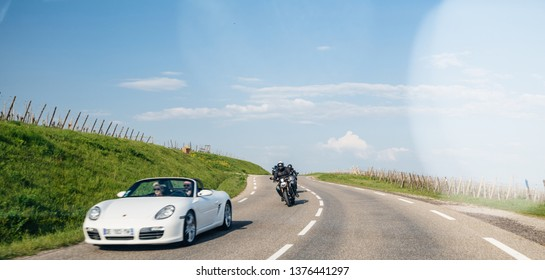 Bergheim, France - Apr 19, 2019: Group of motorcyclists following couple driving in white luxury convertible Porsche sport car driving fast on Alsatian village road