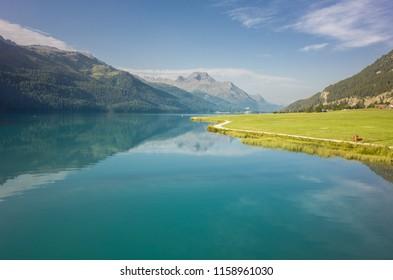 Am Bergsee führt ein Weg durch das grüne Gras. Im Hintergrund sieht man die Alpen.