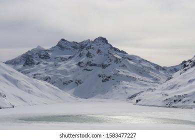 Bergsee zum Teil die Sonne spiegelnd liegt halb gefroren vor dem Hintergrund einer winterlichen weißen Berglandschaft