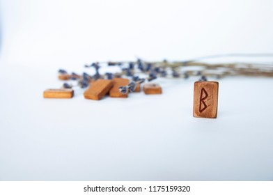 Berkanan. Scandinavian runes. Wooden runes on a table on a white background.