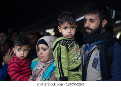 BERKASOVO, SERBIA - OCTOBER 17, 2015: Family of refugee, man and woman, holding their children, waiting to cross the Croatia Serbia border, on the Balkans Route, during the Refugee Crisis