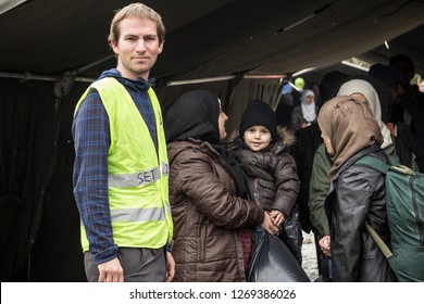 BERKASOVO, SERBIA - OCTOBER 17, 2015: NGO Volunteer standing with a family with a baby waiting to cross the Serbia Croatia border in Berkasovo Bapska, on Balkans Route, during  Refugee Crisis