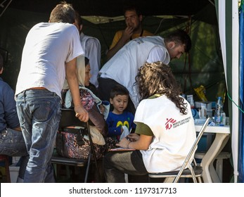 BERKASOVO, SERBIA - OCTOBER 3, 2015: Medecins Sans Frontieres doctors discussing with a refugees family crossing border with Croatia. MSF is an NGO providing doctors in humanitarian situations