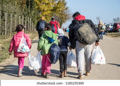 BERKASOVO, SERBIA - OCTOBER 31, 2015: Refugees walking carrying heavy bags on the Croatia Serbia border, between the cities of Bapska and Berkasovo on the Balkans Route, during the Refugee Crisis