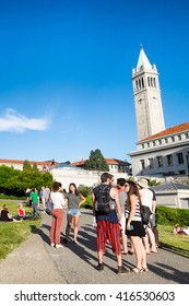 BERKELEY, CA- Apr 16, 2016: Students at the University of California Berkeley campus enjoying a warm spring day outdoors. The iconic Campanile tower is seen in the background. Vertical. Copy space.