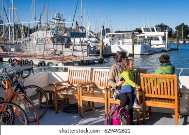 BERKELEY, CA- April 14, 2017: Ferry boat with passengers leaves the Berkeley Marina for San Francisco. A mother and kids are shown sitting in wooden deck chairs, and commuter bikes are stacked.