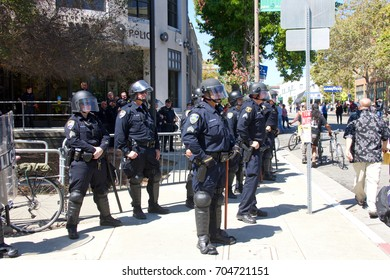 Berkeley, CA - August 27, 2017: Police in riot gear standby as the NO TO MARXISM IN AMERICA rally in Martin Luther King Jr. Civic Center Park proceeds, more counter-protesters than protesters.