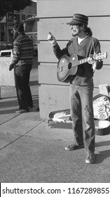 Berkeley, California / USA - December 14, 1985: A busker playing his guitar for tips on Telegraph Avenue in Berkeley, California, December 14, 1985.