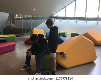 Berkeley, California/USA - September 2, 2018: Two boys sit on colorful cubes as they play games on their phones
