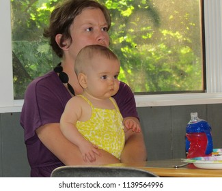 Berkeley Springs, WV, USA - 7/5/2012: an eight-month-old baby and mother both concentrate on the person speaking to them