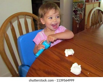 Berkeley Springs, WV, USA - 7/6/2012: a one and a half year old girl enjoys playing with her artificial dough