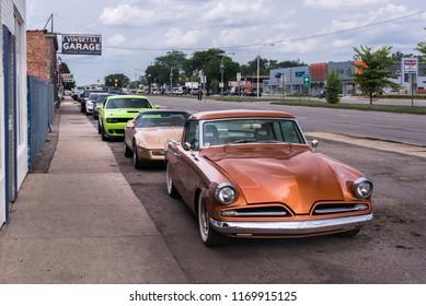 BERKLEY, MI/USA - AUGUST 16, 2018: Three classic cars in front of historic Vinsetta Garage, at Woodward Dream Cruise:  1953 Studebaker Commander Chevrolet C4 Corvette Dodge (SRT) Challenger Hellcat