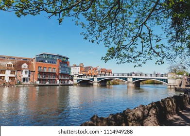 Berkshire, UK - April 2018: The River Thames flowing through Windsor and Eton, twin towns, in Berkshire, in the South East of England, joined by Windsor Bridge