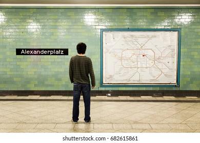 Berlin -  17 JUN: Man waiting on the Alexanderplatz U-Bahn station platform, along with the city railway map in Berlin, Germany on 17 June, 2012.