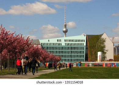 BERLIN, GERMANY—APRIL 22, 2016: People stroll around the Berlin Wall East Side Gallery in Berlin, Germany on a sunny spring day. The iconic TV tower rises up in the distance.