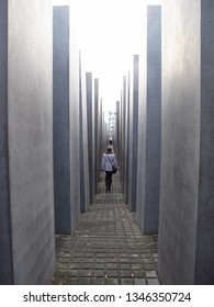 BERLIN, GERMANY—NOVEMBER 25, 2011: A woman walks down a narrow alley between the tall concrete columns of the Memorial to the Murdered Jews of Europe in Berlin, Germany.