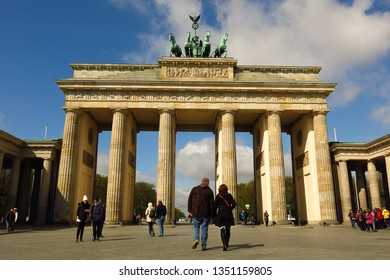 BERLIN, GERMANY—APRIL 25, 2016: People stroll around the Brandenburg Gate in Berlin, Germany's Pariser Platz on a sunny day.