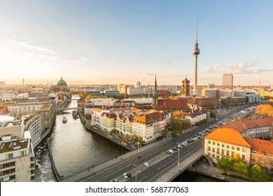 Berlin aerial view at sunset. Berlin Cathedral on the left, tv tower on the right. Golden light over Berlin rooftops in the late afternoon. Travel and architecture concepts