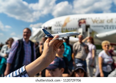BERLIN - APRIL 28, 2018: Airbus A380 toy airplane in children's hands against the backdrop of a real Airbus A380. Exhibition ILA Berlin Air Show 2018.