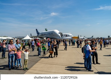 BERLIN - APRIL 28, 2018: Visitors to the exhibition on the airfield. In the background, outsize cargo freight aircraft Airbus A300-600ST or Beluga. Exhibition ILA Berlin Air Show 2018.