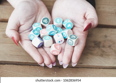 BERLIN, APRIL 5, 2018: Young business person holding cubes with logos of multiple social network websites, symbolic image for management of online public relation through multiple channels.