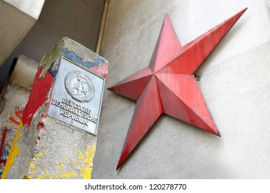 BERLIN - AUGUST 2: German Democratic Republic sign and red star on August 2, 2012 in Berlin. Column and Berlin wall portion near Checkpoint Charlie between east and west sectors during the Cold War.