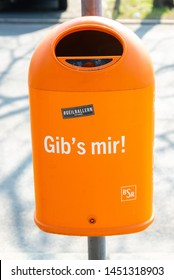"Berlin, Berlin/Germany - 23.03.2019: A garbage can of the BSR (Berliner Stadtreinigung) in orange with the inscription ""Give it to me"""